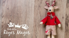 Handmade vintage Christmas deer on wooden background. Lots of copyspace